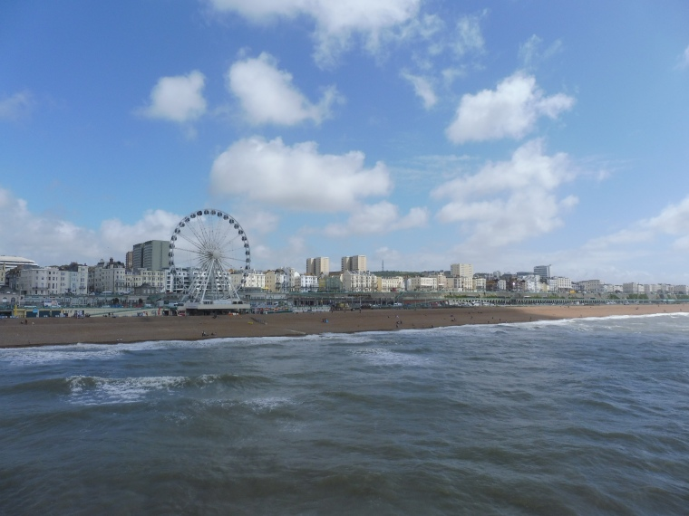 The shoreline and the Brighton ferris wheel seen from a long way down the pier boardwalk.